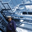 Oil and gas workers with refinery pipelines — Stock Photo #76787891