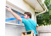 Man Taping His Windows — Stock Photo