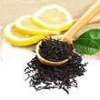 Black tea in a wooden spoon and green lemon leaves. — Stock Photo #52164269