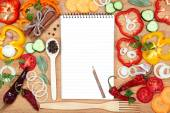 Vegetables, spices and notepad for recipes, on wooden table. — Stock Photo