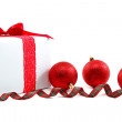 White gift box with red ribbon and christmas balls around. — Stock Photo #54097965