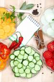 Vegetables, spices and notepad for recipes, on wooden table. — Zdjęcie stockowe