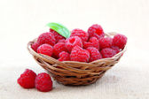 Raspberries in a basket on a homespun cloth.  — Stock Photo