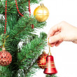 Female hand with red bell and Christmas tree. — Stock Photo #63558865