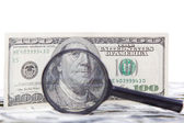 Hundred dollar bill and magnifying glass. — Stock Photo