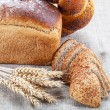 Rye bread, wheat loaf with poppy seeds and ears on sacking. — Stock Photo #68216467