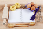 Baking ingredients for cooking and notebook for recipes on a woo — Stock Photo