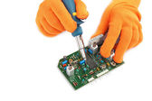 Soldering iron in hand and electric board. — Stock Photo