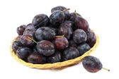 Fresh plums in a basket on a white background. — 图库照片