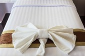 White Towel folded in bow shape on bed — Stock Photo
