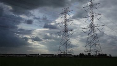 Electric pole, High voltage towers and sky sunset in rice green filed dolly shot — Stock Video
