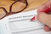 Accident report application form and human hand with pen on brow — Stock Photo