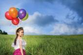 Young asia girl holds tightly to a large bunch of helium filled  — Stock Photo