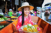 Child sit on the boat and hold the fruit basket — Stock Photo