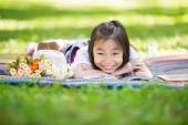 Funny little Asian girl reading and learning with tablet pc — Stock Photo