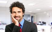 Knappe zakenman in zijn kantoor — Stockfoto