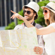 Couple of tourists holding map — Stock Photo #54317855
