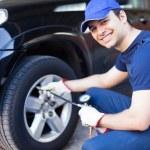 Mechanic inflating tire — Stock Photo #54319649