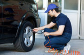 Smiling mechanic inflating tire — Stock Photo
