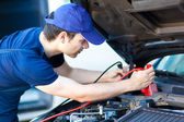 Auto electrician troubleshooting car engine — Stock Photo