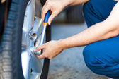 Mechanic inflating tire — Stockfoto