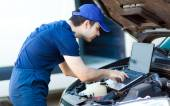 Mechanic using laptop to check car engine — Stock Photo