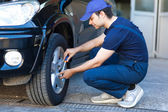 Mechanic inflating tire — Stock Photo