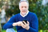 Mature man using cell phone — Stockfoto
