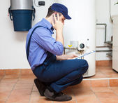 Technician servicing an hot-water heater — Stock Photo