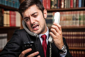 Businessman talking on many phones — Stock Photo