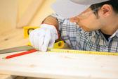 Carpenter using measuring tape — Stock Photo