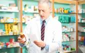 Pharmacist taking bottle of pills — Stock Photo