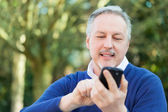 Mature man using cell phone — ストック写真