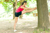 Woman stretching leg against tree — Stock Photo