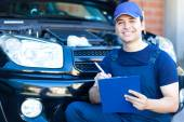 Smiling mechanic writing on clipboard — Stock Photo