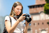 Smiling female tourist taking photos — Stockfoto