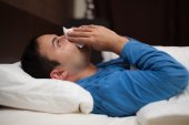 Ill man blowing nose in bed — Stock Photo