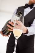 Waiter pouring champagne into flute — Stock Photo
