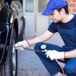 Mechanic inflating tire — Stock Photo #55358947