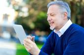 Mature man using tablet at park — Foto Stock