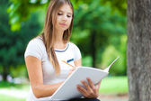 Female student on bench in park — Stock Photo
