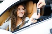 Woman receiving keys of car — Stockfoto