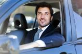 Smiling business man driving car — Stockfoto