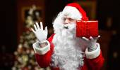 Santa Claus in costume holding gift — ストック写真