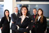 Businesswoman in front of business people — Stock Photo
