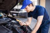 Auto electrician working on car engine — Stock Photo