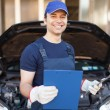 Mechanic holding a clipboard in front of a car — Stock Photo #61558545