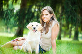 Woman playing with her her golden retriever outdoors — Stock Photo