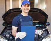 Mechanic holding a clipboard in front of a car — Stock Photo
