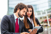 Business people using a digital tablet — Stock Photo